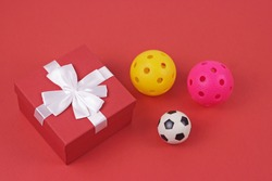 Christmas red giftbox with white ribbon and sport balls on red surface. Shopping concept boxing day and black Friday sale composition.