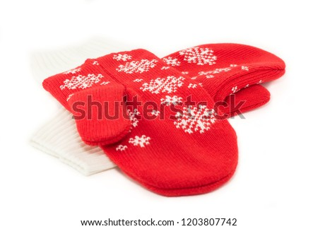 Christmas red knitted mittens with snowflake motives on white background. Pair of red woolen gloves, isolate on white   #1203807742