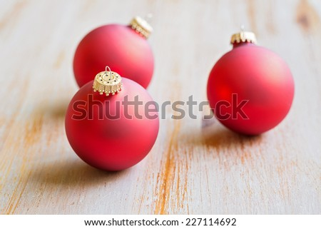 christmas red ornaments on a sun bleached wooden background