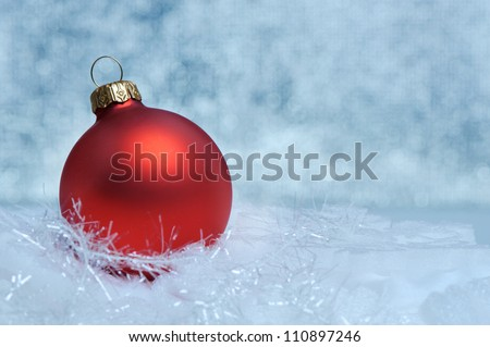 Christmas red sphere. Bokeh background blue toned