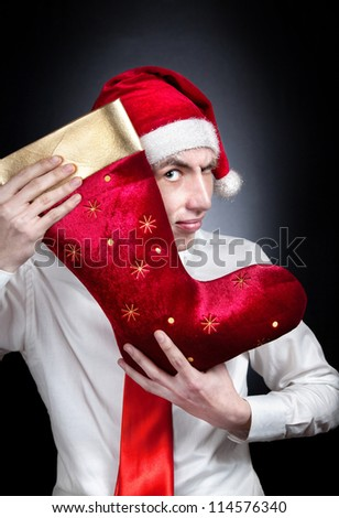 Christmas red stocking and young teen in Christmas hat and white shirt with red tie at black background