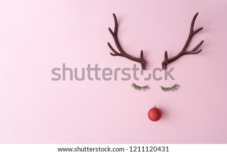 Christmas reindeer concept made of evergreen fir, red bauble decoration and antlers on pastel pink background. Minimal winter holidays idea. Flat lay top view composition. - Shutterstock ID 1211120431