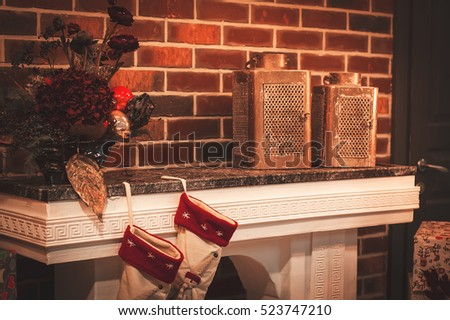 Christmas room and lighting. Christmas socks on fireplace, decoration, gifts, vintage candles