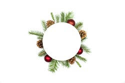 Christmas round frame mockup made of spruce branches, red decorations, fir cones flat lay isolated on white background, copy space. Christmas composition with wreath top view. Xmas celebration