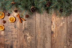 christmas rustic background. Christmas winter holidays greeting template. Christmas tree branches, oranges, cinnamon, anise and cones on dark wooden background with copy space. Flat lay