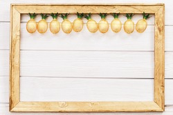 Christmas rustic background with string lights as pineapples golden colored on white in wooden frame. Festive decoration, New Year fairy garland. Flat lay. Top view, copy space.