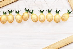 Christmas rustic background with string lights as pineapples golden colored on white wooden. Festive decoration, New Year fairy garland. Flat lay. Top view, copy space.