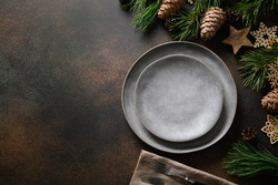 Christmas rustic home table setting with empty gray plate and xmas wooden decor on brown table. Top view, flat lay with copy space.
