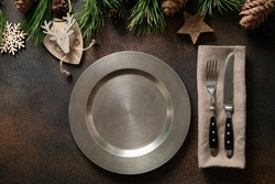 Christmas rustic home table setting with empty plate and xmas wooden decor on brown table. Top view, flat lay.