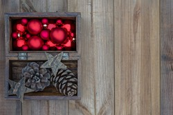 Christmas rustic wooden box with Xmas red balls, cedar cones, wood stars, decorations on wooden background. Vintage Christmas composition. Top view, flat lay, copy space.