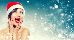 Christmas sale. Beautiful surprised Woman in Santa Claus hat over Xmas Winter Holiday winter background with snow, Emotions. Funny Laughing Woman Portrait. New year sales