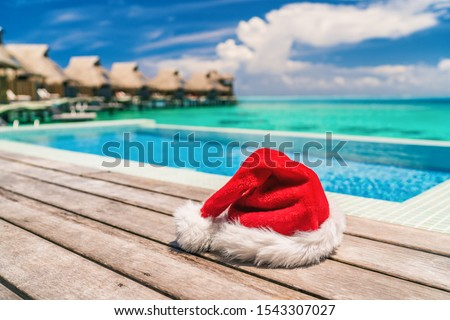 Christmas Santa Claus luxury vacation gift hotel holidays - hat by the infinity swim pool of high end resort for tropical sun vacation getaway during winter holiday. Overwater bungalows villas. #1543307027