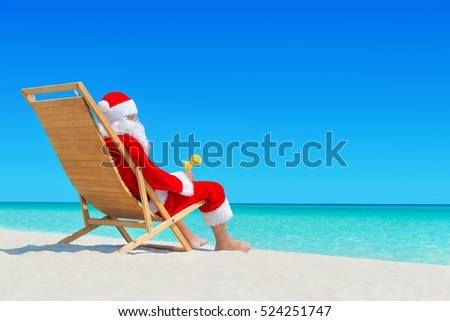 Christmas Santa Claus relax on wooden sunlounger with fresh orange juice cocktail at ocean tropical sandy beach - New Year travel destinations in hot countries concept