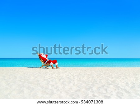 Christmas Santa Claus relaxing on sunlounger at ocean sandy tropical beach under palm leaves. Happy New Year travel destinations to hot countries concept #534071308