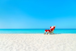 Christmas Santa Claus resting on sunlounger at ocean sandy tropical beach - xmas travel vacation in hot countries concept