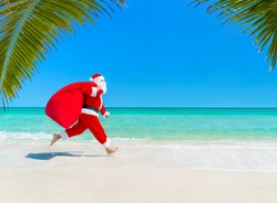 Christmas Santa Claus running at ocean tropical sandy palm beach with large sack full of presents hurry on give it for children  - New Year vacation and travel agencies price concept discounts