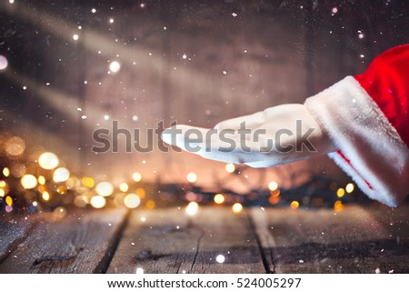 Christmas Santa Claus showing empty copy space on the open hand palm for text. Proposing product. Advertisement gesture presenting point. Holding gift, text or product over wooden background