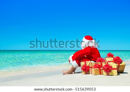 Christmas Santa Claus with golden gift fancy boxes relaxing at ocean tropical beach sand - New Year travel destinations vacation in hot countries travel price discounts concept #515639053
