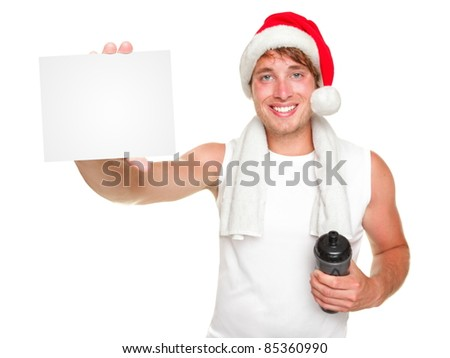 Christmas santa exercise man showing white gift / business card for holiday message. Fit young man wearing santa hat Isolated on white background.