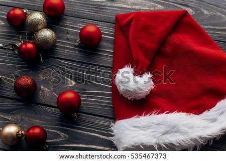 6a67552e1d27e christmas santa hat and red and golden ornaments on rustic wooden background  with space for text