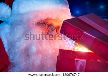 Christmas Santa. Santa Claus opening Magic Gift Box.