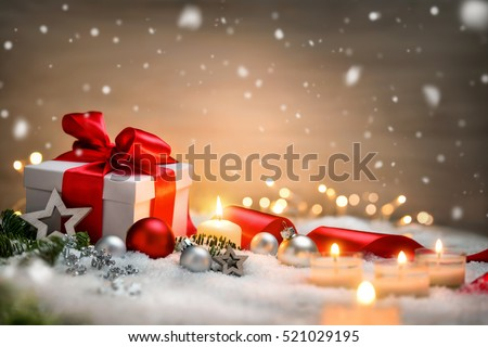 Christmas scene with a white gift box, red bow and ribbon, candles, lights, baubles, fir branches and snow, with copy space #521029195