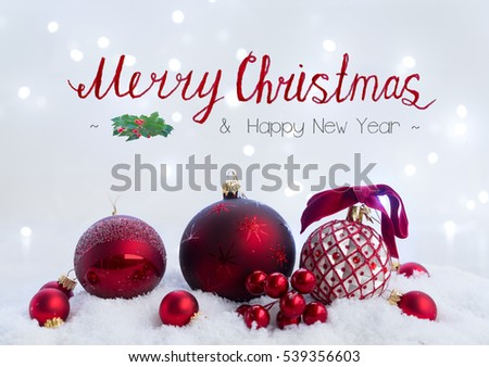 Christmas scene with snow -  red balls with lights in background with merry christmas greetings