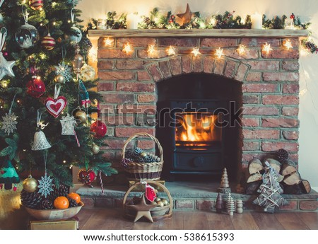 Christmas setting: Christmas tree, decorations in the basket in front of the fireplace, handmade wooden toys made on the wood lathe, selective focus; dark vintage style toned photo