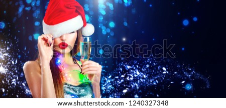 Christmas sexy woman. Beauty model girl in Santa Claus hat with red lips, champagne glass in her hand Celebrating on night club party. Closeup glamour portrait on winter wide background with copyspace