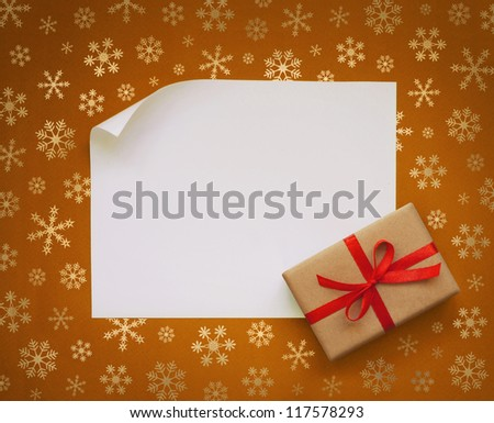 Christmas sheet of paper and small gift with red ribbon on gold snowflakes background