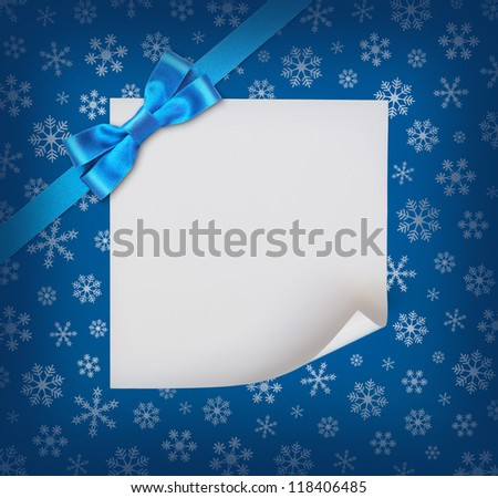 Christmas sheet of paper with blue ribbon bow on blue snowflakes background