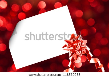 Christmas sheet of paper with bow and ribbons on red defocused background - stock photo