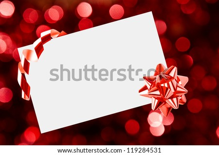 Christmas sheet of paper with bow and ribbons on red defocused background