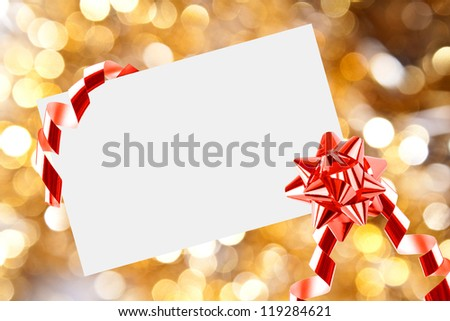 Christmas sheet of paper with bow and ribbons on yellow defocused background