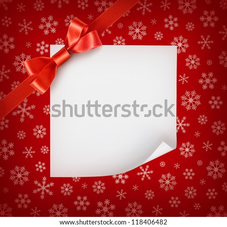 Christmas sheet of paper with red ribbon bow on red snowflakes background