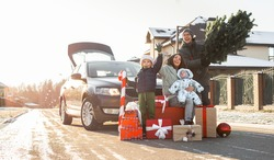 Christmas shopping and family preparation for winter holidays. Happy parents and cheerful children with many gifts and Xmas fir tree outside near car in town or country. Family of four