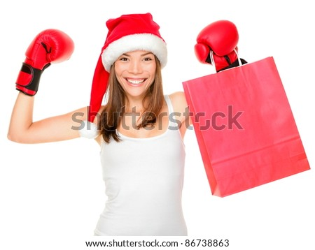 Christmas shopping boxing day concept with woman holding shopping bag wearing santa hat and boxing gloves. Funny fresh image of mixed race Asian Caucasian female model isolated on white background.