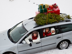 Christmas shopping, celebrating - the family is riding a car with christmas tree and gifts on the roof of the car