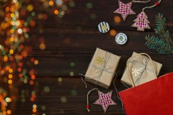 Christmas shopping. Gift red paper bag with kraft paper boxes with golden snowflakes, toys on dark wooden background. Multi-colored bokeh lights. Eco gifts. Copy space. Festive concept