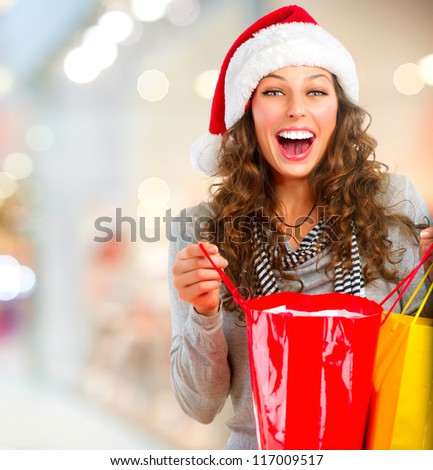 Christmas Shopping. Happy Woman with Shopping Bags in Shopping Mall.Sales. Christmas Gifts.Shopping Mall