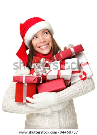 Christmas shopping woman holding gifts smiling happy looking up to side isolated on white background. Santa girl wearing sweater and santa hat holding presents. Mixed race Asian Caucasian female model
