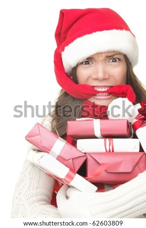 Christmas shopping woman stress. Young shopper holding christmas gifts / presents stressed, frustrated and angry. Funny woman biting her santa hat and arms full of gifts. Isolated on white background.