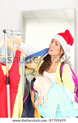 christmas shopping - woman tired. Funny image of woman exhausted from Christmas sales. Young Asian woman wearing Santa hat.