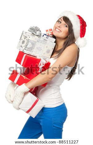 Christmas shopping woman with funny expression holding many gift boxes over white background.