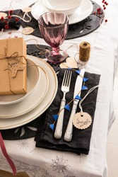 Christmas silverware on a black elegant napkin next to a set of three dishes with a gift box inside and a pretty transparent purple glass. The name Sarah is on a round tag.