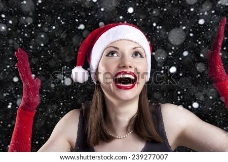 Christmas smiling woman in Santa hat and red gloves with snowflakes on a black background