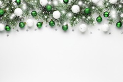 Christmas snow border of shiny white and green balls, evergreen branches on a white wooden background. New year card.