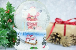 Christmas snow globe with Santa Claus inside surrounded by branches of holly, cones and gift box. Festive Christmas background