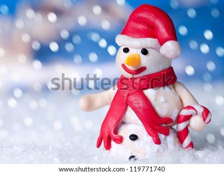 Christmas snowman in santa claus hat at winter