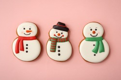 Christmas snowman shaped gingerbread cookies on pink background, flat lay